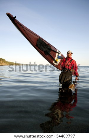 Sea kayaker coming out of the water - stock photo