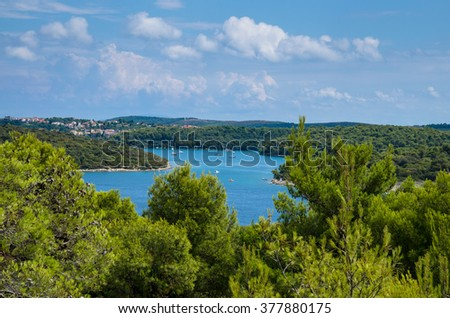 sea lagoon with boats and pine trees around - stock photo