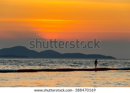 Sea landscape and a female tourism walk on the foam in the sea with sunset time, Pattaya Thailand - stock photo