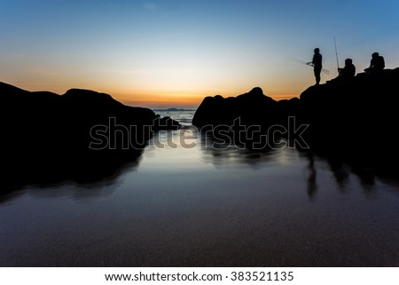 sea landscape and fisherman stand on rock at beach with sunset time, Pattaya Thailand - stock photo