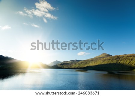 Sea landscape, vivid sunset. Calm sea. Cliffs on the horizon. Faroe Islands. - stock photo