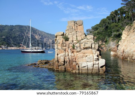 Sea landscape with a rock and small yacht