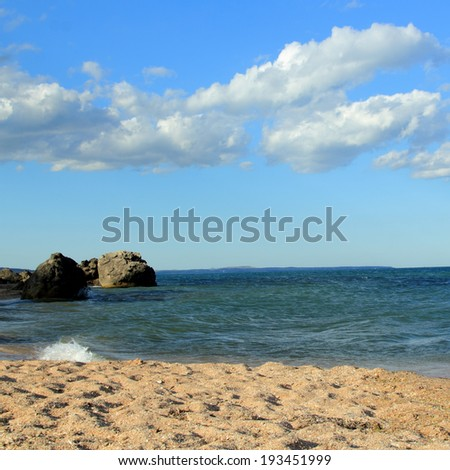 Sea landscape with big stones in the sea and on the shore on a sunny summer day