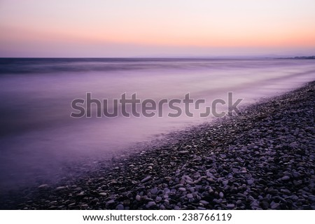 Sea long exposure of sea and rocks. Purple and pink sunset. Pebble beach, foggy water. - stock photo