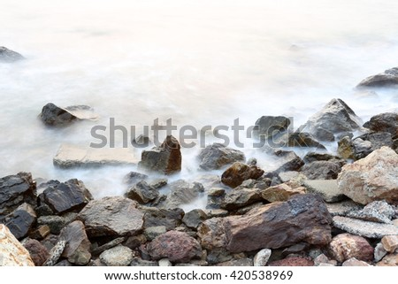 Sea mist softness of the tides and sunset at evening with rocks in foreground,viewpoint in Chanthaburi Thailand. - stock photo