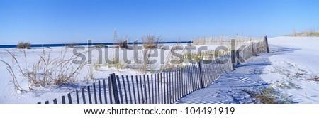 Sea oats and fence along white sand beach at Santa Rosa Island near Pensacola, Florida - stock photo