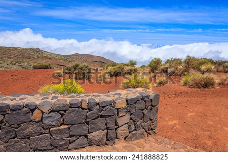 Sea of clouds and wall built of lava stone in Teide National Park, Tenerife, Canary Islands, Spain - stock photo