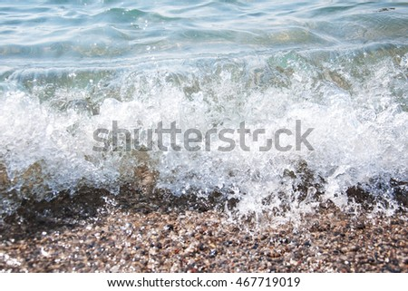 sea pebble on beach and sea water - nature background