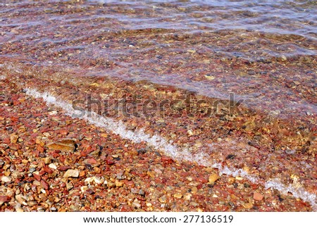 Sea pebble - sea wave on gravel beach, selective focus for background. - stock photo