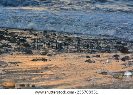 Sea pebbles washed by the waves at sunset - stock photo