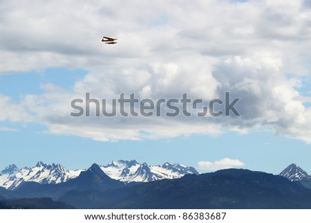 Sea plane flying in the clouds over the Kenai Mountains in Alaska - stock photo