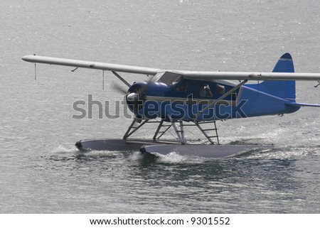 sea plane taxiing to the dock - stock photo
