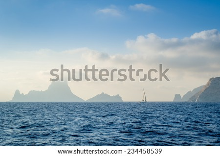 Sea rocks and sailing boat in the fog seascape in the Mediterranean sea, near Ibiza island - stock photo