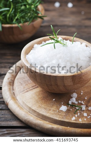 Sea salt and fresh rosemary on the wooden table, selective focus