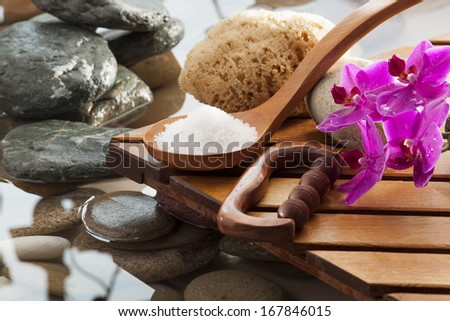 sea salt and massage tools next to water