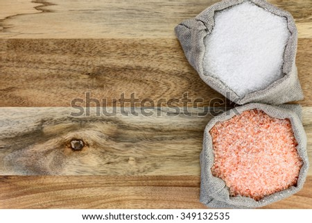 Sea salt and pink salt in the linen sacks on the wooden background - stock photo