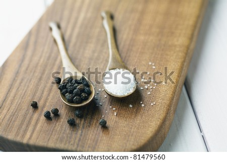 Sea salt and whole pepper on wooden spoons. - stock photo
