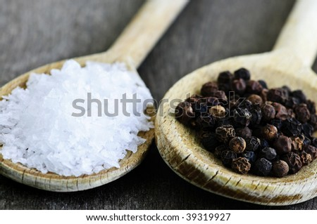Sea salt and whole peppercorns on wooden spoons - stock photo