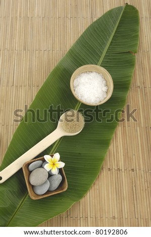 Sea salt bath in spoon with and stones on banana leaf