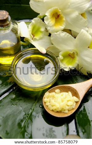 Sea salt bath in spoon with orchid and massage oil on monstera leaf