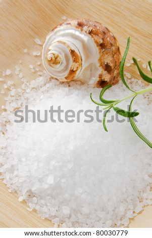 Sea salt bath scrub accented with aromatic rosemary and a seashell on a bamboo tray