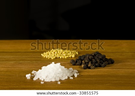 Sea Salt, Black Pepper and Mustard Seeds on wooden board. Black background allows for creative uses. - stock photo
