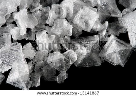 sea salt crystals flakes on black background, super macro shot, shallow DOF - stock photo