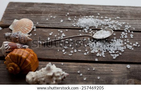 sea salt crystals in a silver spoon on a rustic wooden table - stock photo