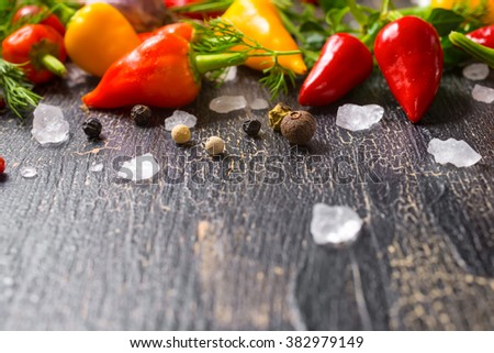 sea salt, dry spices, yellow, red hot chili peppers, different greenery, on cracks black background - stock photo