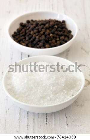 Sea salt flakes and black peppercorns, in small white dishes over weathered timber.