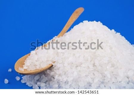Sea salt heap and wooden spoon on blue background - stock photo