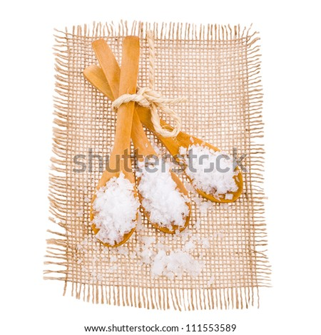 Sea salt in a large three wooden spoons lying on a small mat, isolated on white background - stock photo