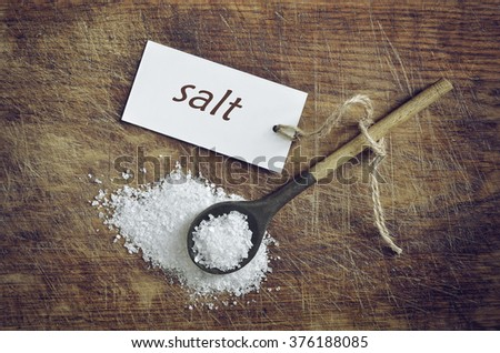 Sea salt in a spoon on vintage wooden background, top view - stock photo