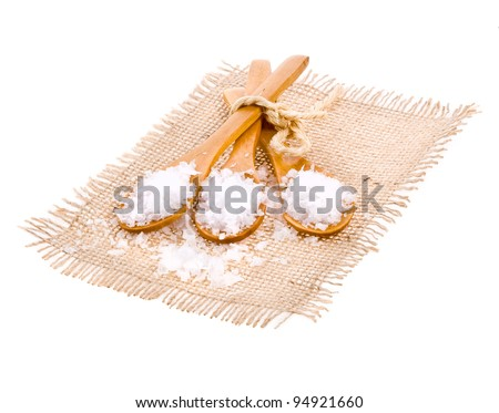 Sea salt in a wooden spoons . - stock photo
