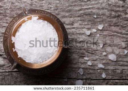 sea salt in an old utensils on wooden table - stock photo