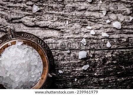 sea salt in an old utensils on wooden table - stock photo
