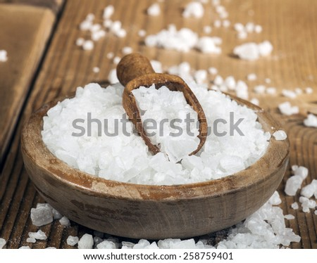Sea salt in bowl and spoon on a wooden background.