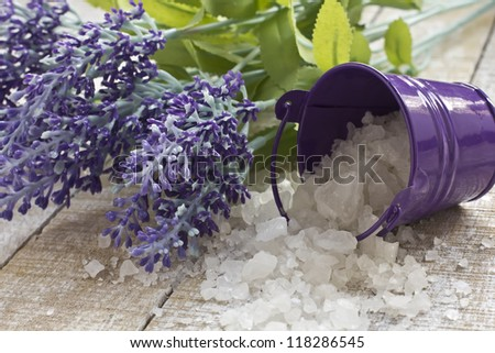 Sea salt in little bucket and lavender on white wooden background. Selective focus. - stock photo