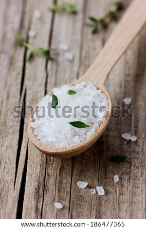 Sea salt in spoon with a fresh herbs thyme on a wooden rustic surface - stock photo