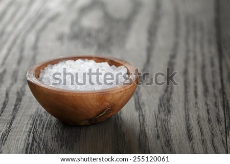 sea salt in wooden bowl for cooking or spa, on dark table - stock photo