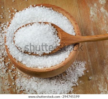 Sea salt in wooden bowl. Selective focus - stock photo