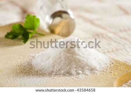 Sea salt on cloth and wooden plate in kitchen. - stock photo