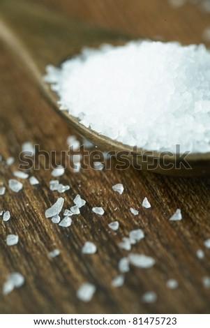 Sea salt on wooden spoon. - stock photo