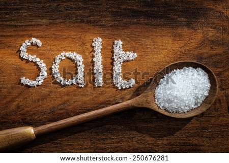 Sea salt on wooden spoon and the word salt written in grain - stock photo