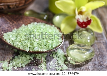 Sea salt on wooden spoon, orchid flowers in the background - stock photo