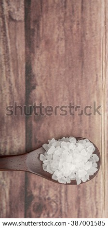 Sea salt on wooden spoon over wooden background