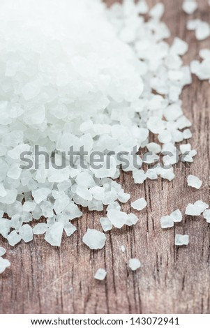 Sea salt over wooden background, selective focus, close up - stock photo