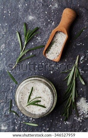 Sea salt scented herb rosemary on black stone background, vintage style, top view - stock photo