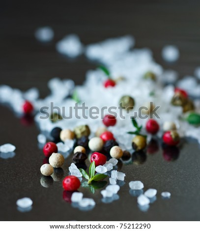 Sea salt, thyme and colorful peppercorns on a shiny black. - stock photo