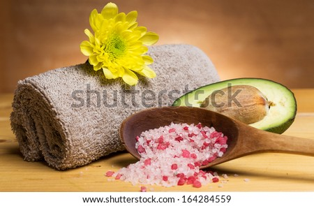 Sea salt, towel and avocado over wooden background - stock photo